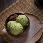 Green tea matcha ice cream scoops with sweet red bean paste in dark brown bowl over wooden plate with green tea powder on bamboo plate mat on wood table, Japanese style sweet, flat lay (top view)
